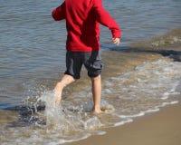 Τρεξίματα μη αναγνωρίσιμα παιδιών κατά μήκος της ακτής στα γυμνά πόδια, SP Στοκ Εικόνα