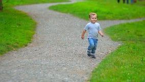 Τρεξίματα μικρά αγοριών μέσω του πάρκου απόθεμα βίντεο