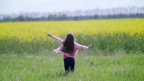 Τρεξίματα μικρών κοριτσιών στον κίτρινο τομέα απόθεμα βίντεο