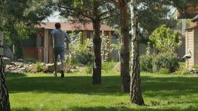 Τρεξίματα νεαρών άνδρων μέσω του χορτοτάπητα στον κήπο απόθεμα βίντεο