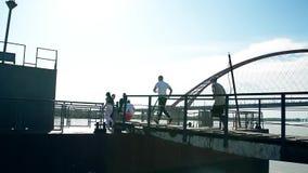 Τρεξίματα ομάδας ανθρώπων στη γέφυρα Νεολαία στην παραλία Οι φίλοι που έχουν τη διασκέδαση ευτυχή χαλαρώνουν την κατοχή του παιχν απόθεμα βίντεο