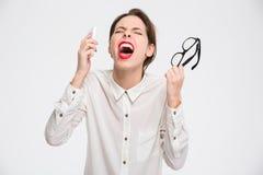 Τρελλή απελπισμένη επιχειρησιακή γυναίκα με το smartphone και την κραυγή γυαλιών Στοκ φωτογραφίες με δικαίωμα ελεύθερης χρήσης