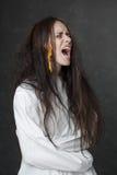 Τρελλή γυναίκα που κραυγάζει σε έναν περισταλτικό μανδύα Στοκ Εικόνες