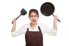 Τρελλός ασιατικός μάγειρας κοριτσιών με το τηγάνισμα του τηγανιού Στοκ Φωτογραφίες