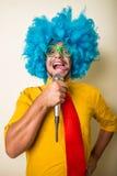 Τρελλός αστείος νεαρός άνδρας με την μπλε περούκα Στοκ Φωτογραφία