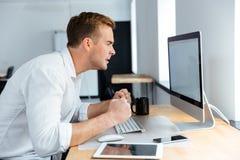 Τρελλός ενοχλημένος επιχειρηματίας που εργάζεται με τον κενό υπολογιστή οθόνης στην αρχή Στοκ Εικόνες