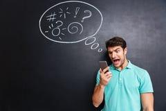 Τρελλός εξαγριωμένος νεαρός άνδρας που χρησιμοποιεί το smartphone και να φωνάξει Στοκ Εικόνα