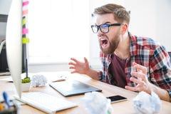Τρελλός επιθετικός σχεδιαστής ατόμων που κοιτάζει στο όργανο ελέγχου και να φωνάξει Στοκ φωτογραφία με δικαίωμα ελεύθερης χρήσης