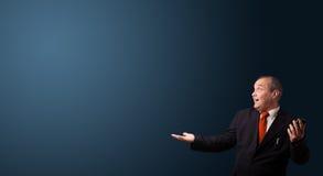 Τρελλός επιχειρηματίας που κρατά ένα τηλέφωνο και που παρουσιάζει το διάστημα αντιγράφων Στοκ Φωτογραφία