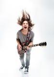 Τρελλός νεαρός άνδρας που τινάζει την επικεφαλής και ηλεκτρική κιθάρα παιχνιδιού Στοκ εικόνα με δικαίωμα ελεύθερης χρήσης