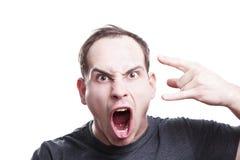 Τρελλός ο νεαρός άνδρας φωνάζει και παρουσιάζει βράχο - και - σημάδι χεριών ρόλων Στοκ Εικόνες