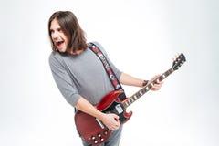 Τρελλός συγκινημένος νεαρός άνδρας που κραυγάζει και που παίζει την ηλεκτρική κιθάρα Στοκ Φωτογραφίες