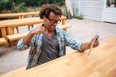 Τρελλό ενοχλημένο αφρικανικό άτομο στα γυαλιά και τα ακουστικά που χρησιμοποιούν την ταμπλέτα Στοκ φωτογραφία με δικαίωμα ελεύθερης χρήσης