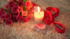Τριαντάφυλλα ανθοδεσμών, κορδέλλα και μήκος σε πόδηα καψίματος κεριών για την ημέρα βαλεντίνων απόθεμα βίντεο