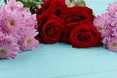 Τριαντάφυλλα και χρυσάνθεμα στο ξύλινο υπόβαθρο Στοκ Εικόνα