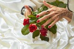 Τριαντάφυλλα καλά-καλλωπισμένα στα ηλικιωμένη γυναίκα χέρια Στοκ Φωτογραφίες