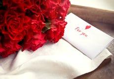 Τριαντάφυλλα και κάρτα για την ημέρα του βαλεντίνου Στοκ Φωτογραφίες
