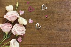 Τριαντάφυλλα πλαισίων και καρδιές εγγράφου πέρα από την ξύλινη σύσταση Στοκ φωτογραφία με δικαίωμα ελεύθερης χρήσης