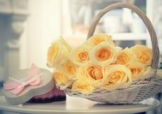 Τριαντάφυλλα σε ένα ψάθινο καλάθι και ένα δώρο Στοκ Εικόνες