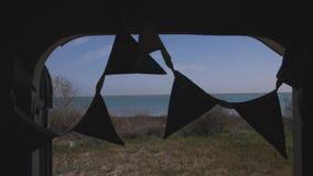 Τριγωνικές σημαίες που ταλαντεύονται στον αέρα στην πόρτα του ρυμουλκού ενάντια στο σκηνικό της λίμνης απόθεμα βίντεο