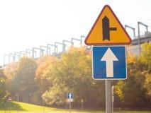 Τριγωνικό σημάδι κυκλοφορίας που δείχνει μια στροφή ευθεία μια κύρια οδός που τοποθετείται σε έναν πόλο ακρών του δρόμου ενάντια  στοκ εικόνες