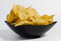 Τριζάτα τσιπ πατατών σε ένα μαύρο κύπελλο σε ένα άσπρο υπόβαθρο Στοκ Φωτογραφίες