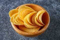 Τριζάτα τσιπ σε ένα ξύλινο κύπελλο σε έναν γκρίζο σκοτεινό πίνακα snack στοκ εικόνα