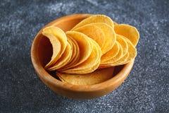 Τριζάτα τσιπ σε ένα ξύλινο κύπελλο σε έναν γκρίζο σκοτεινό πίνακα snack στοκ φωτογραφίες με δικαίωμα ελεύθερης χρήσης