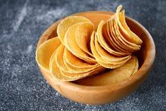 Τριζάτα τσιπ σε ένα ξύλινο κύπελλο σε έναν γκρίζο σκοτεινό πίνακα snack στοκ εικόνα με δικαίωμα ελεύθερης χρήσης
