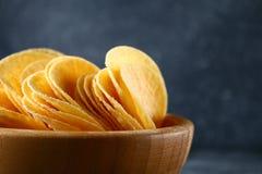 Τριζάτα τσιπ σε ένα ξύλινο κύπελλο σε έναν γκρίζο σκοτεινό πίνακα snack στοκ φωτογραφίες