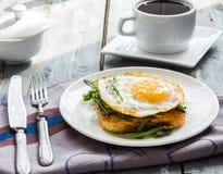 Τριζάτη φρυγανιά με ένα τηγανισμένο αυγό και ένα φρέσκο arugula, ένα φλιτζάνι του καφέ Στοκ Φωτογραφίες