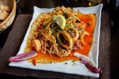 Τριζάτο κινεζικό πιάτο νουντλς με τα θαλασσινά, ψάρια, γαρίδα, καλαμάρι Στοκ Φωτογραφία