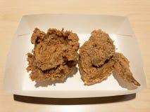 Τριζάτο τηγανισμένο κοτόπουλο σε ένα κιβώτιο της Λευκής Βίβλου στοκ εικόνα