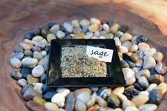 Τριμμένη φασκομηλιά σε ένα μικρό μαύρο πιάτο με την ετικέτα Στοκ Φωτογραφίες