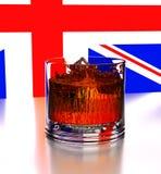 τρισδιάστατος Κύβοι της παγόπτωσης σε ένα γυαλί με το ουίσκυ Το υπόβαθρο είναι ένα τεμάχιο της αγγλικής σημαίας Παφλασμός, σκιά,  Στοκ φωτογραφία με δικαίωμα ελεύθερης χρήσης