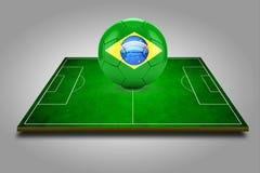 τρισδιάστατη εικόνα του πράσινων γηπέδου ποδοσφαίρου και της ποδόσφαιρο-σφαίρας με το λογότυπο της Βραζιλίας Στοκ εικόνα με δικαίωμα ελεύθερης χρήσης