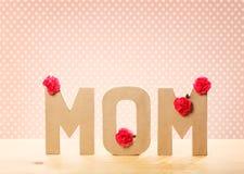 τρισδιάστατο κείμενο MOM με τα λουλούδια γαρίφαλων στον πίνακα Στοκ φωτογραφίες με δικαίωμα ελεύθερης χρήσης