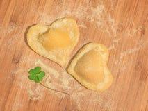 Τριφύλλι με ακατέργαστο χειροποίητο ravioli δύο με μορφή της καρδιάς, που καλύπτεται με το αλεύρι και που τοποθετείται στον ξύλιν Στοκ εικόνες με δικαίωμα ελεύθερης χρήσης