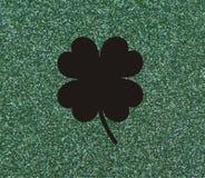 Τριφύλλι με τέσσερα φύλλα, μαύρα σε ένα πράσινο υπόβαθρο glittery Στοκ φωτογραφίες με δικαίωμα ελεύθερης χρήσης
