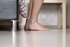 Τριχωτά πόδια ατόμων δίπλα στο κρεβάτι στοκ φωτογραφίες