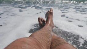 Τριχωτά πόδια ατόμων στην κυματωγή θάλασσας Διασχισμένα γυμνά πόδια φιλμ μικρού μήκους