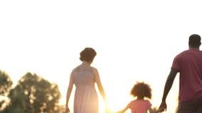 Τριών ατόμων οικογένεια που περπατά στο ηλιοβασίλεμα, ευτυχές μέλλον μαζί, μνήμες στοκ φωτογραφία με δικαίωμα ελεύθερης χρήσης