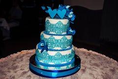 Τριών επιπέδων γαμήλιο κέικ με την μπλε μαστίχα και μπλε καρδιές στο γαμήλιο εορτασμό, για τα newlyweds Στοκ εικόνα με δικαίωμα ελεύθερης χρήσης