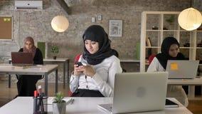 Τριών νέων μουσουλμανικών γυναικών στη συνεδρίαση και τη δακτυλογράφηση hijab στο lap-top στο σύγχρονο γραφείο, γοητευτική γυναίκ απόθεμα βίντεο