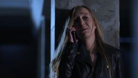 Τρομαγμένη γυναίκα που μιλά με 911 στο smartphone απόθεμα βίντεο