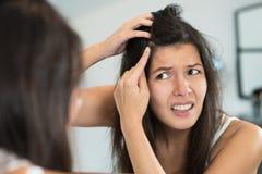 Τρομαγμένη νέα γυναίκα που κοιτάζει στον καθρέφτη Στοκ Φωτογραφία