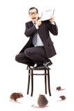 Τρομαγμένος επιχειρηματίας που στέκεται στην καρέκλα που υπερασπίζεται από το ρ στοκ εικόνα με δικαίωμα ελεύθερης χρήσης