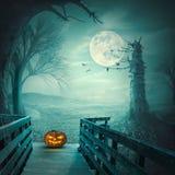 Τρομακτική κολοκύθα αποκριών στην ξύλινη γέφυρα στη νύχτα πανσελήνων στοκ φωτογραφίες