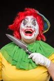 Τρομακτικός πλακατζής κλόουν με ένα χαμόγελο και κόκκινη τρίχα με ένα μεγάλο μαχαίρι επάνω Στοκ Εικόνες