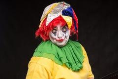 Τρομακτικός πλακατζής κλόουν με ένα χαμόγελο και κόκκινη τρίχα σε ένα μαύρο backgroun Στοκ εικόνες με δικαίωμα ελεύθερης χρήσης